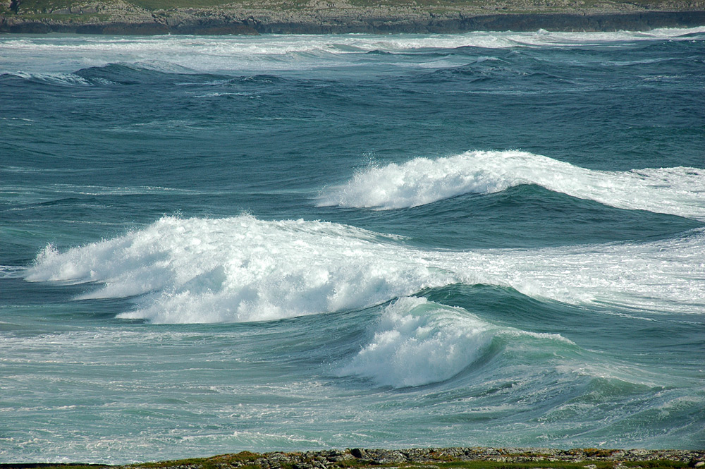 Picture of waves breaking as they roll into a bay