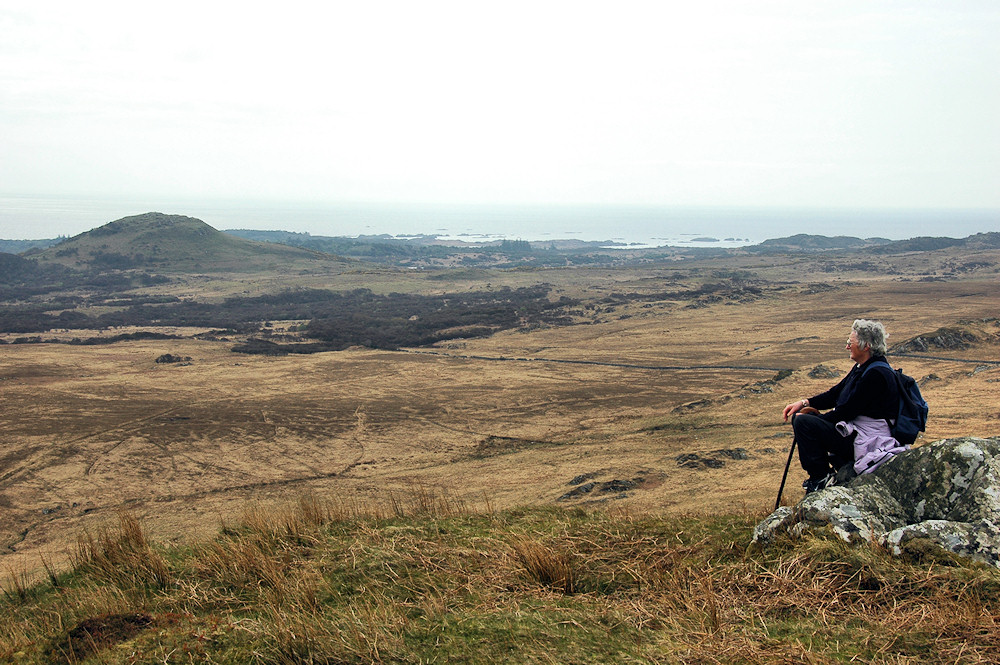 Picture of a walker sitting on a rock on a hill, enjoying the view