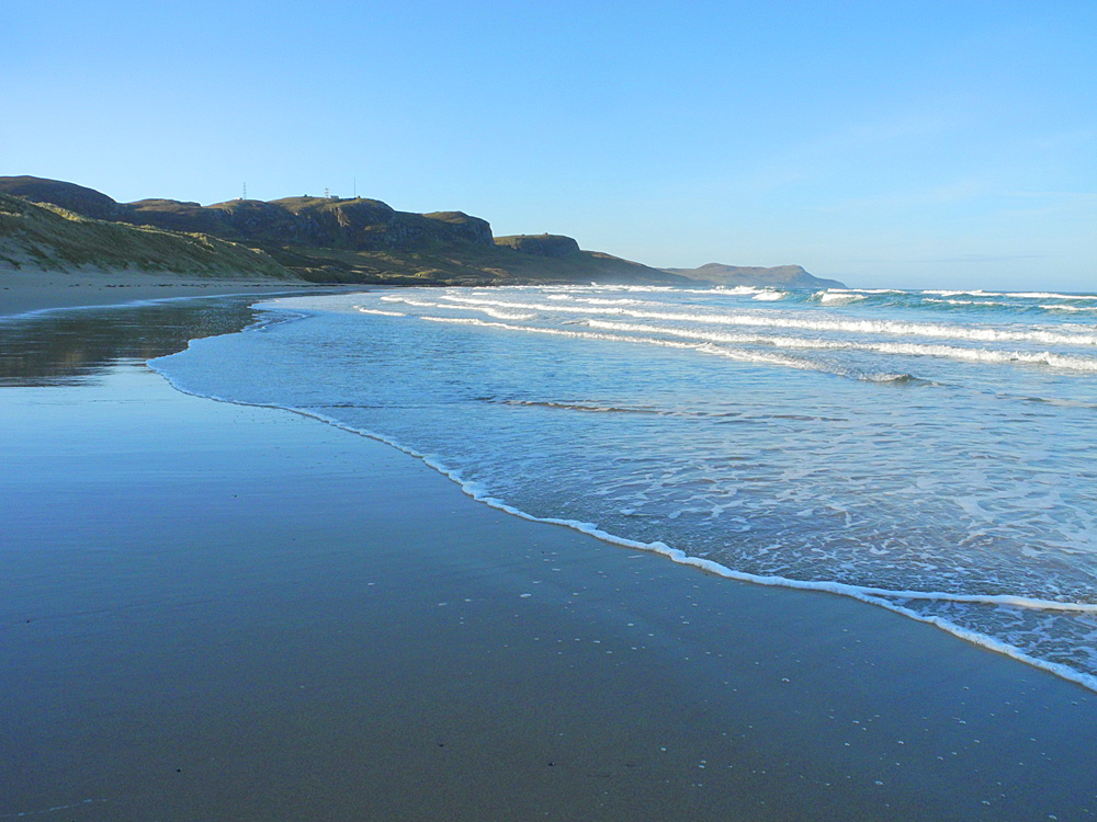 Picture of a bay with a sandy beach and waves rolling in on a sunny April morning