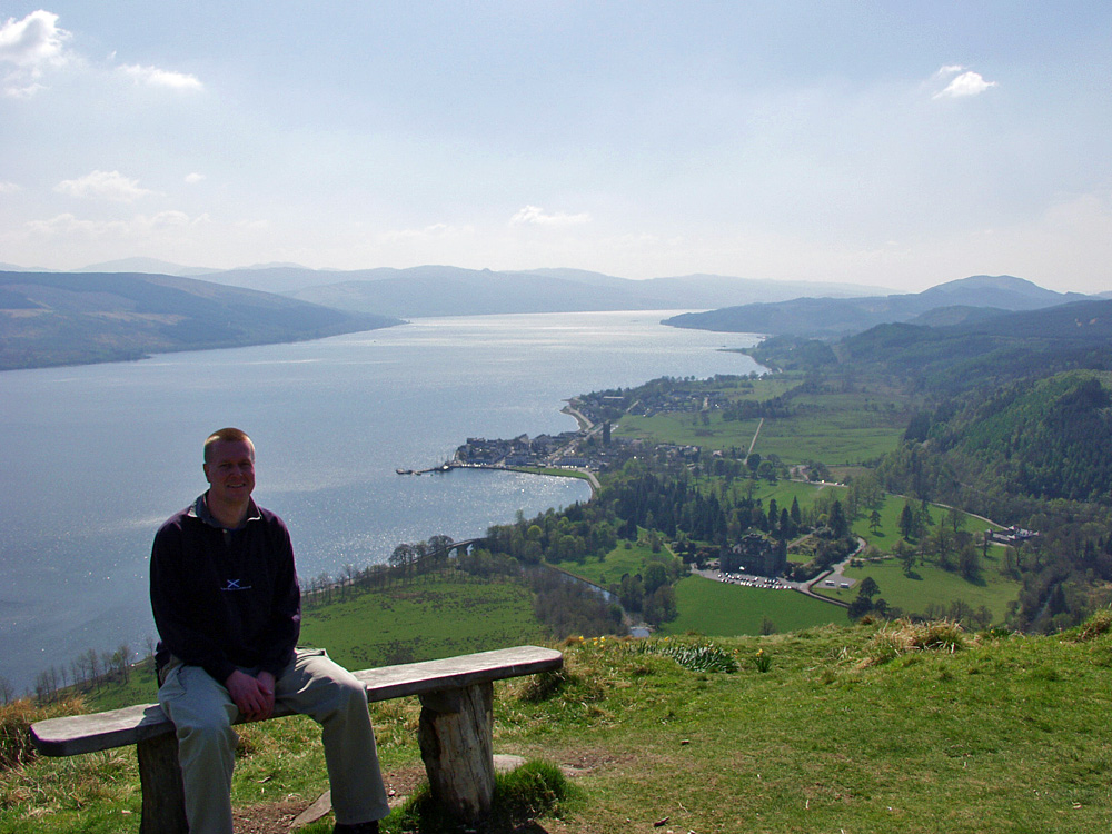 Picture of a man sitting on a bench high above a sea loch, a coastal village below