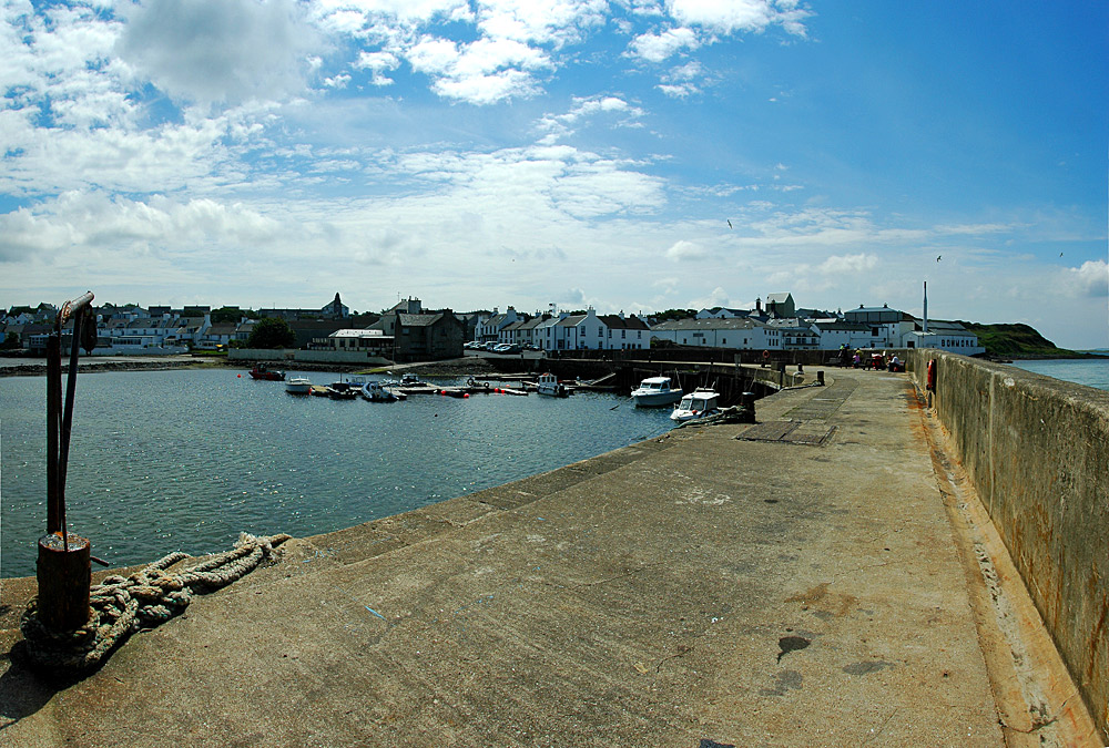 Panoramic picture of a view over a small harbour at a coastal village with a distillery