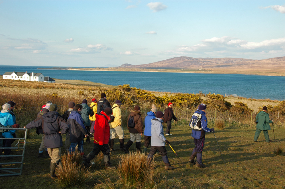 Picture of a group of walkers approaching a sea loch in beautiful evening sunshine