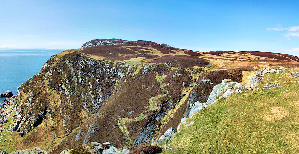 Picture of a coastal landscape with cliffs and plateaus, a group of hillwalkers almost disappearing in the vastness