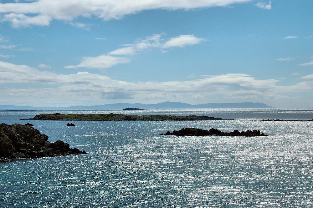 Picture of a view over a few skerries across the sea to the mainland