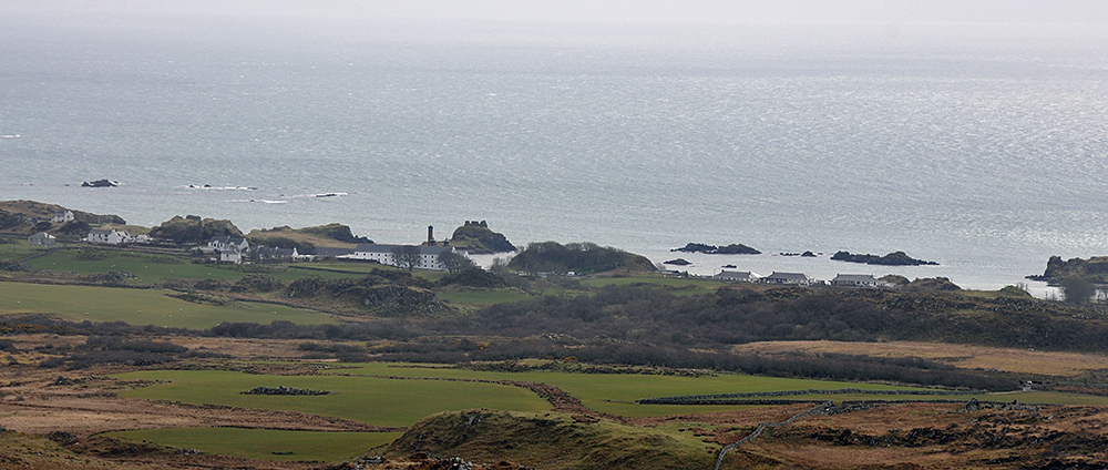 Picture of a coastal village with a distillery, seen from the hills behind