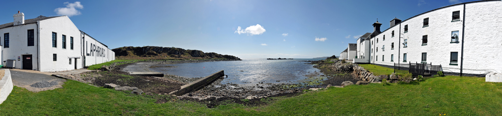 Panoramic picture of a small sea loch next to a distillery