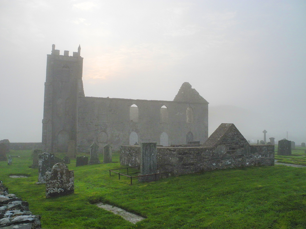 Picture of the ruin of a church in the morning mist, the sun starting to break through