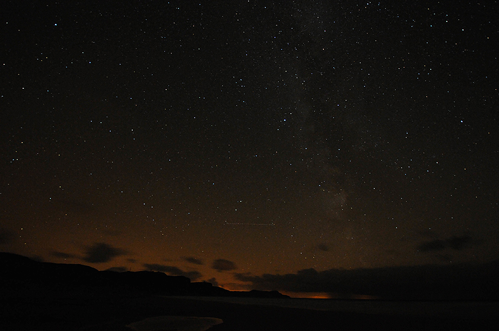 Picture of stars in the night sky over a bay with a beach