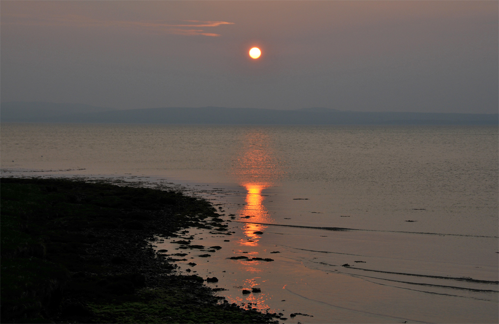 Picture of a sunset at a sea loch on a hazy evening