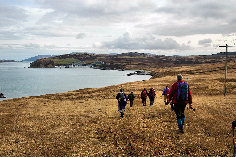 Picture of a group of walkers walking towards a distillery at a small bay at a sound