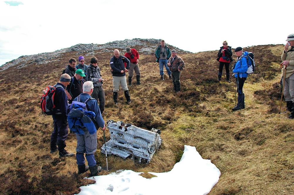 Picture of a group of hillwalkers standing around the engine of a crashed plane