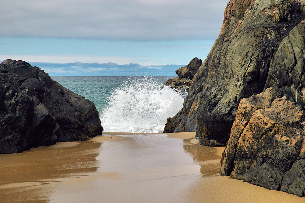 Picture of a wave splashing between two rocks on a sandy beach