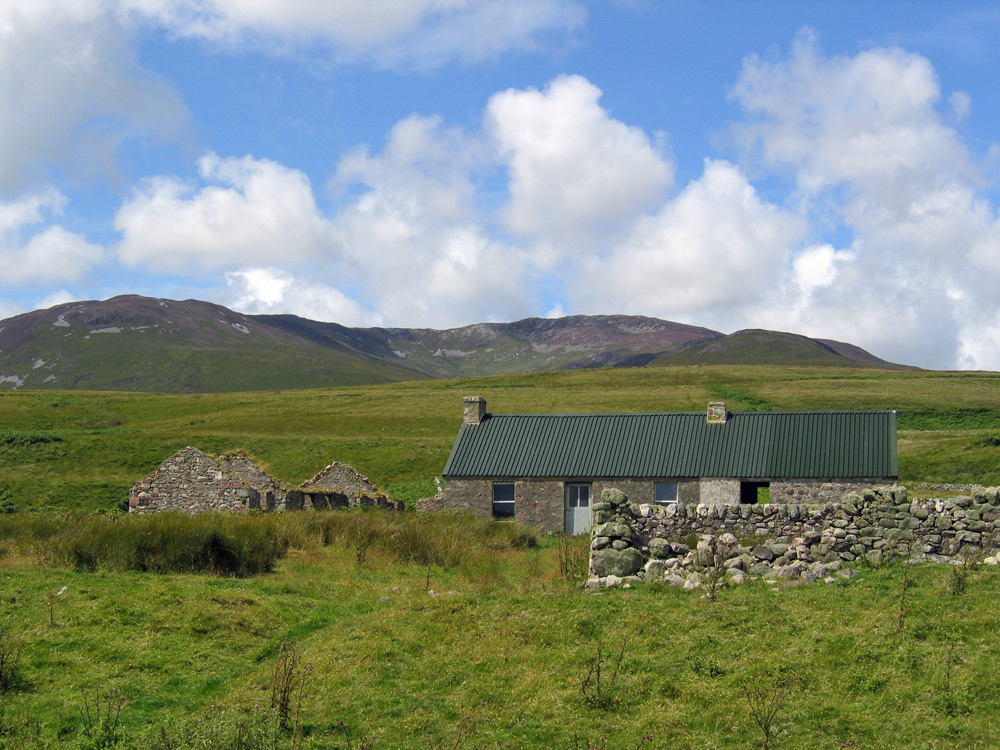 Picture of a bothy in a converted old farm building, ruins around the bothy, a large hill in the background