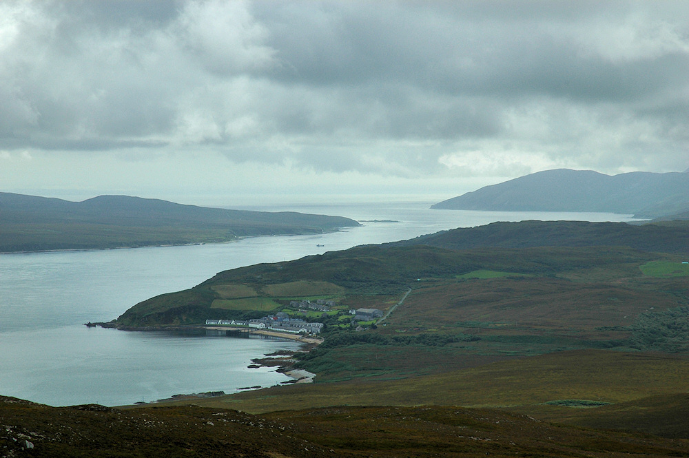 Picture of a view over a sound between two islands from a hill, a distillery below