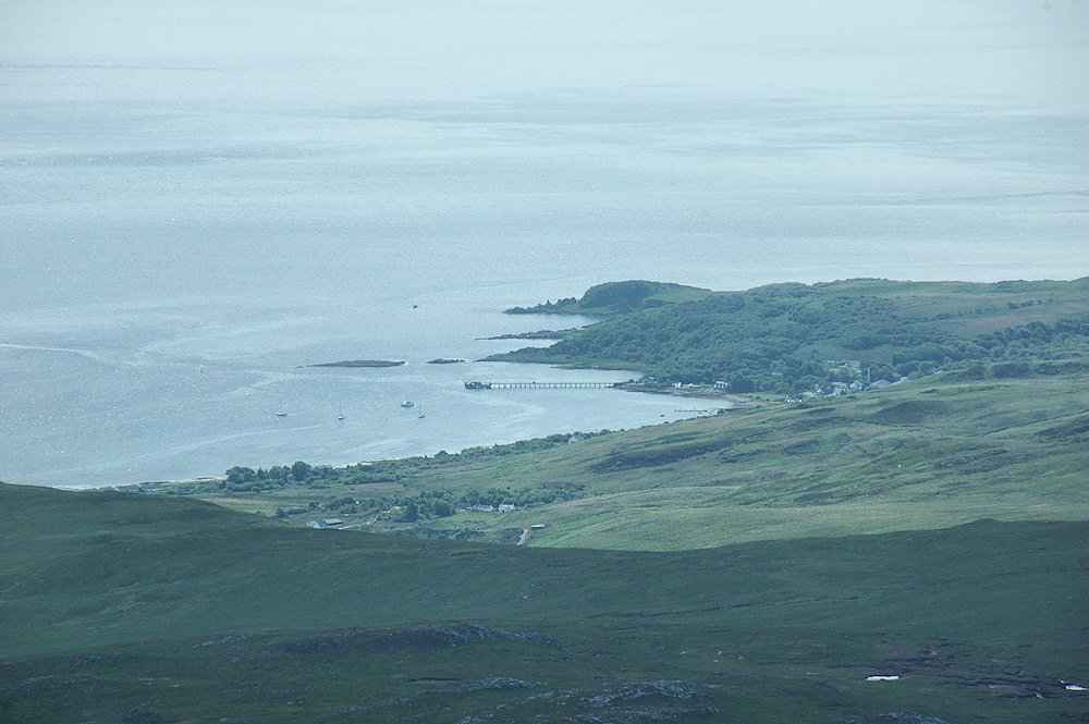 Picture of a small coastal village with a long pier, seen from a mountain above the village