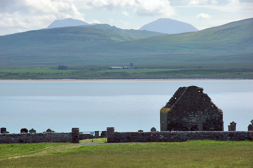 Picture of a ruined church, a sea loch, a farm and dramatic mountains