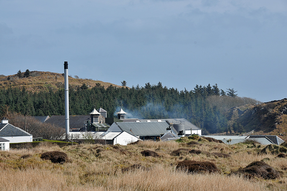 Picture of the roofs of a distillery, seen behind low hills