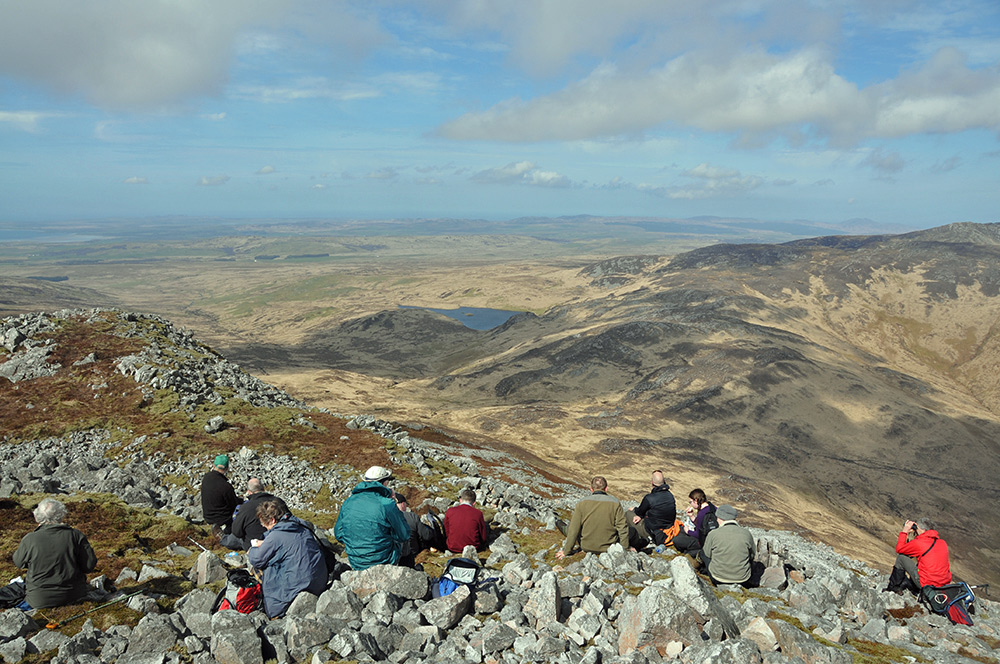Picture of walkers having lunch at the summit of a hill