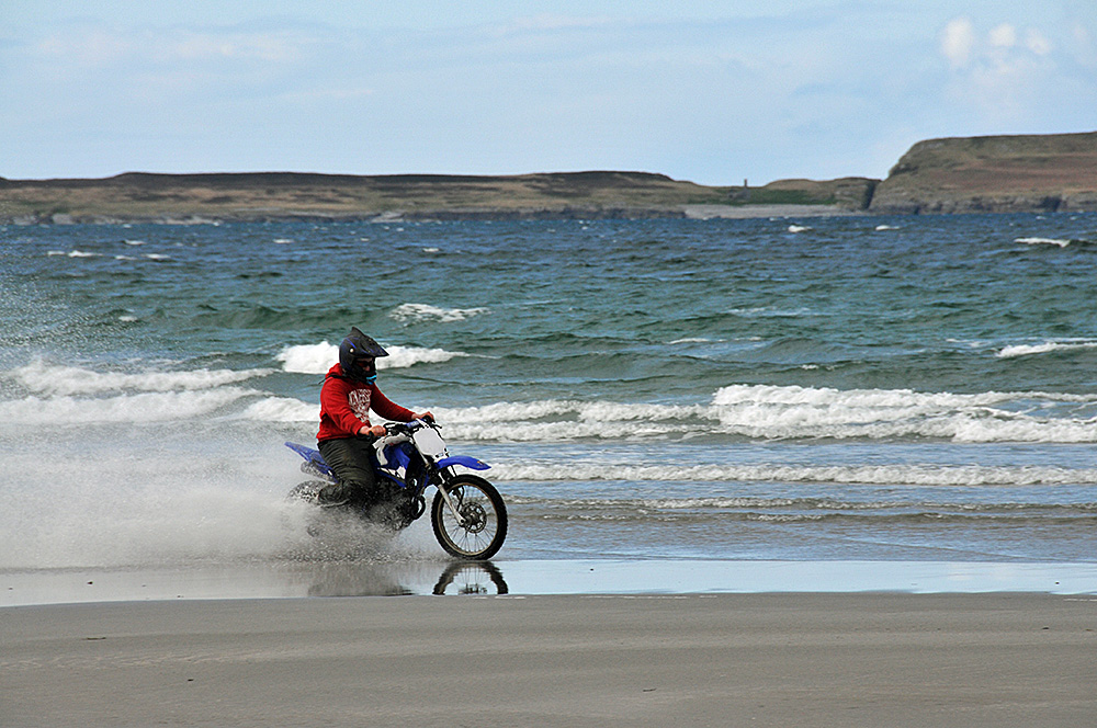 Picture of a man on a motocross bike on a beach