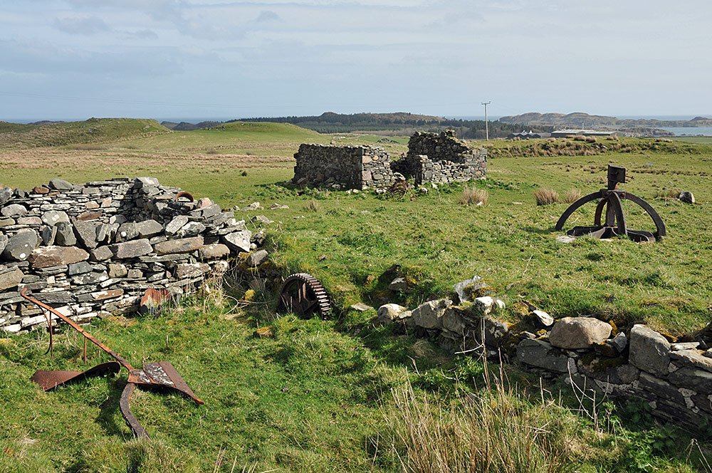 Picture of the ruins of an old farm with some rusting farm machinery, a distillery visible in the distance