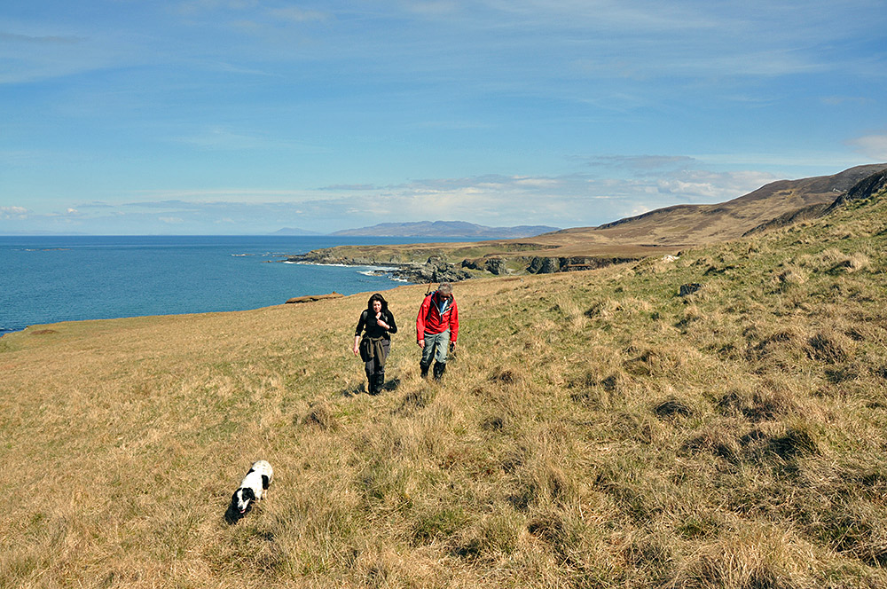 Picture of two walkers and a dog on a coastline with raised beaches