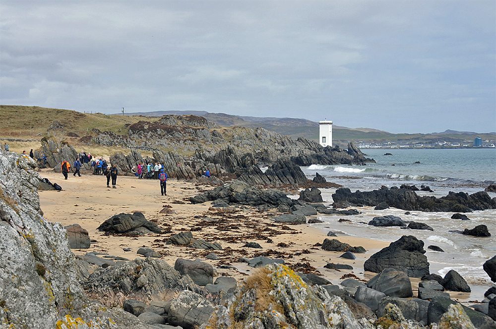 Picture of a group of walkers on a beach, a lighthouse and a village in the background