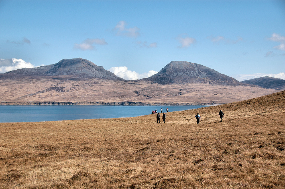 Picture of a group of walkers approaching a sound between two islands, two mountains on the other side of the sound