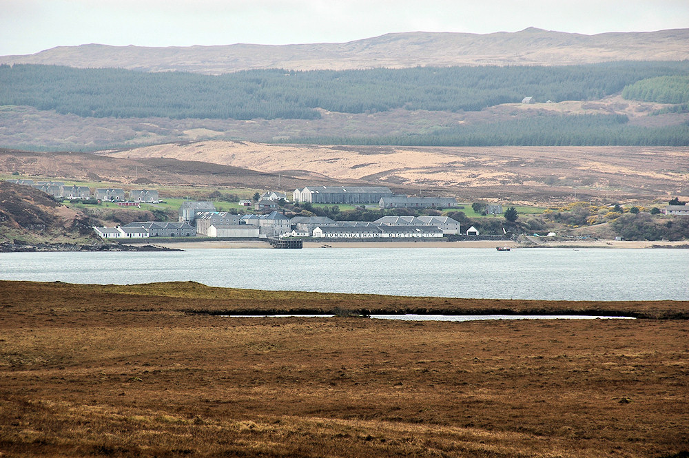 Picture of a distillery with a small village, seen across a sound between two islands