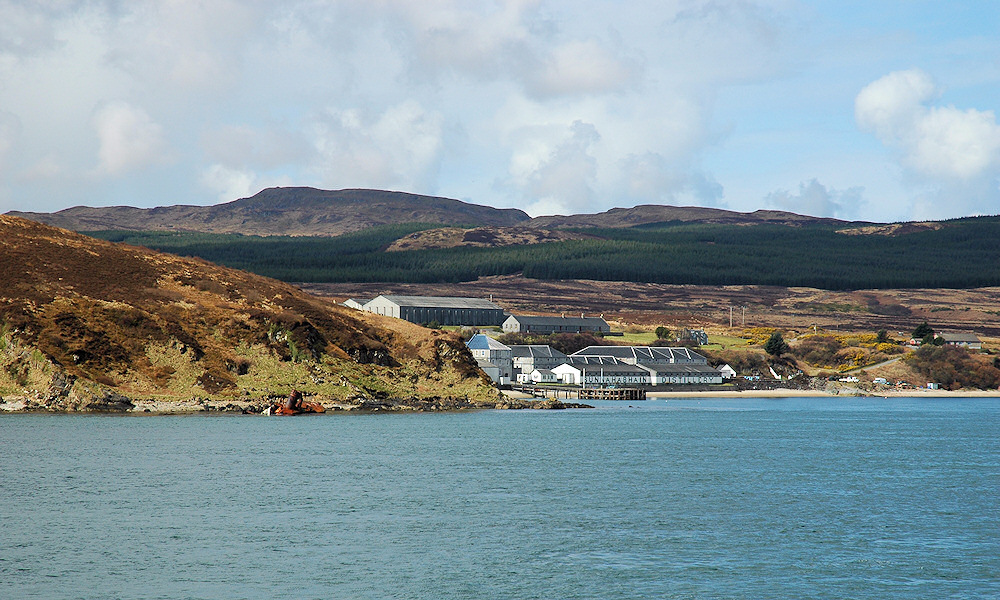 Picture of a coastal distillery with the wreck of a fishing trawler on a nearby shore