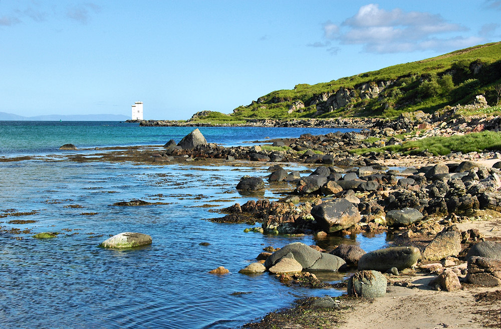 Picture of a square lighthouse at a rocky shore