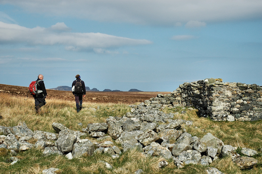 Picture of two walkers in a wide open landscape, close to a ruin with collapsed walls