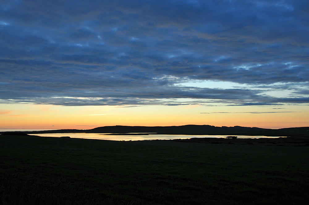 Picture of a freshwater loch in the last evening light, clouds above but clear in the distance