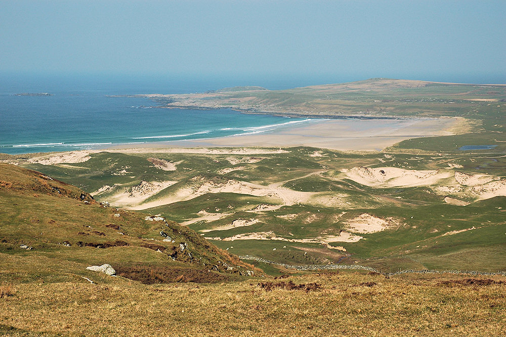 Picture of a view over a bay with a wide sandy beach, dunes in the foreground