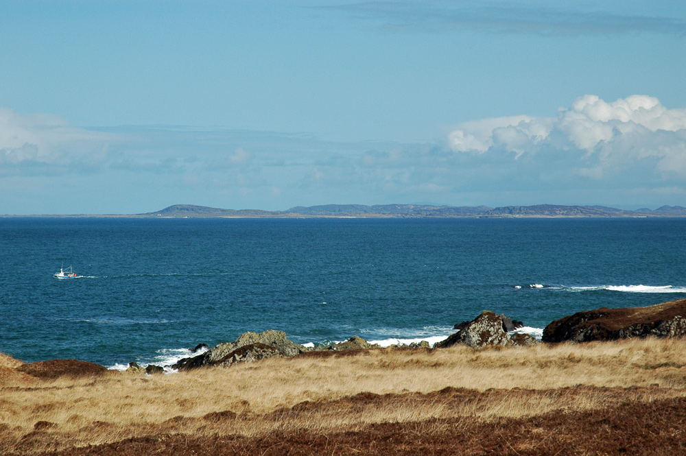 Picture of two islands seen across the sea from an island