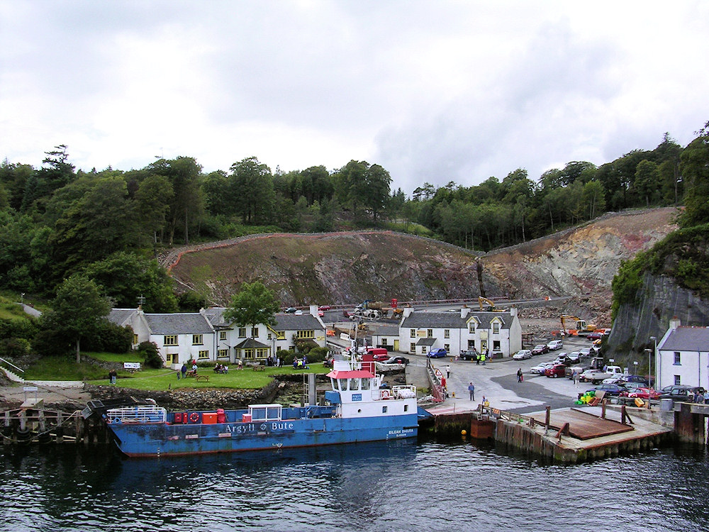 Picture of a small harbour with a new road being built into the hill behind it