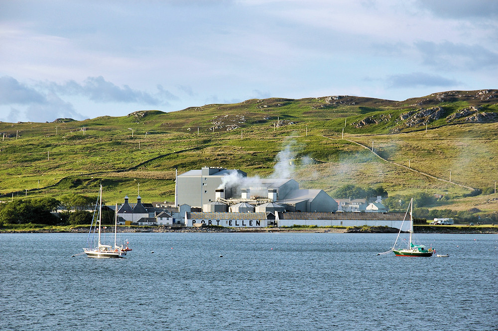 Picture of the Port Ellen Maltings with two sailing yachts moored in the bay in front
