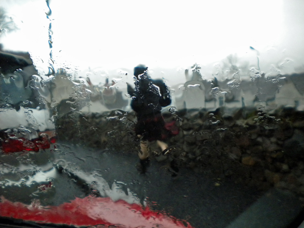 Picture of a view out of a car in a rain, a man in a kilt walking past