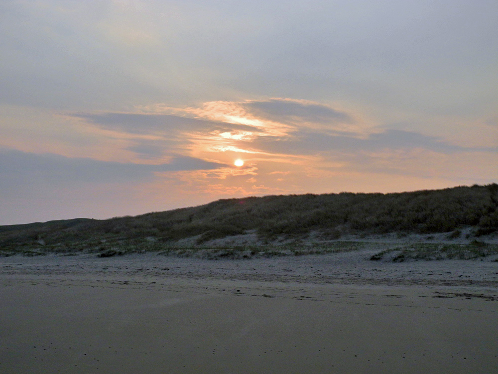 Picture of a view to dunes from a beach with the sun rising behind the dunes