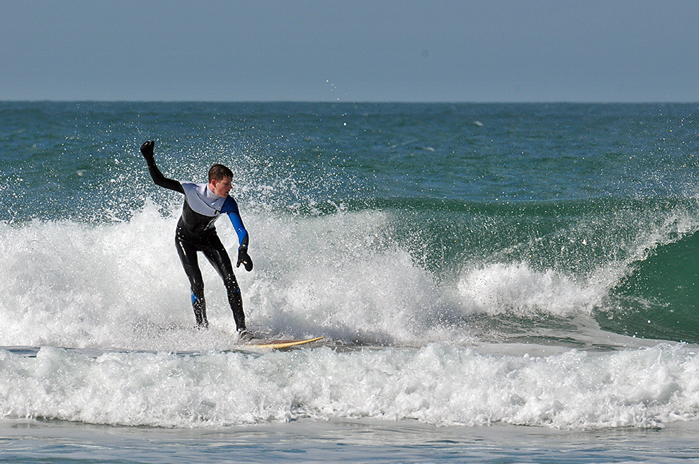 Picture of a young man surfing a wave on a sunny day