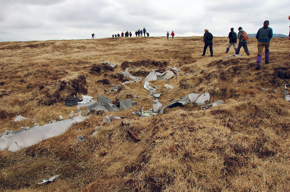 Picture of a group of walkers passing the remains of an old plane wreck