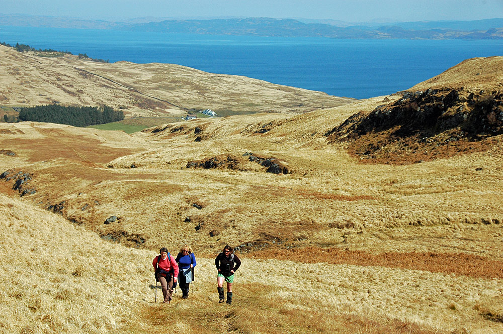 Picture of three walkers walking up a hill on an island