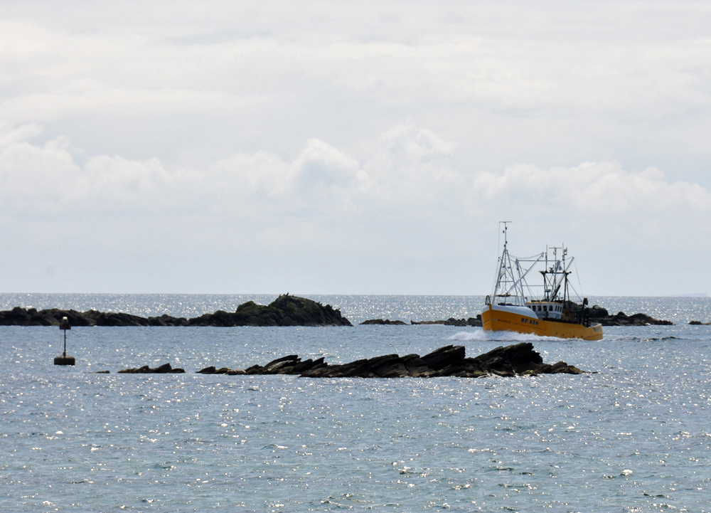Picture of a yellow fishing boat cruising through a narrow entrance