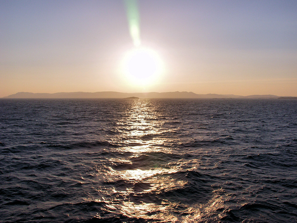 Picture of the sun low in the sky over an island, seen from a ferry