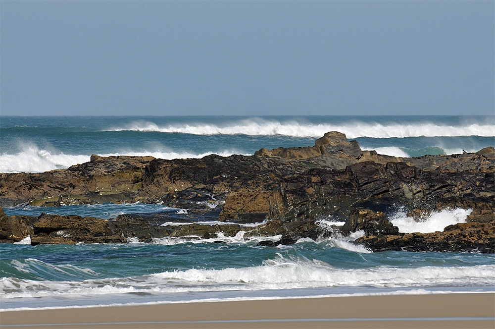 Picture of a beach with rocks, waves rolling in with the spray blown backwards