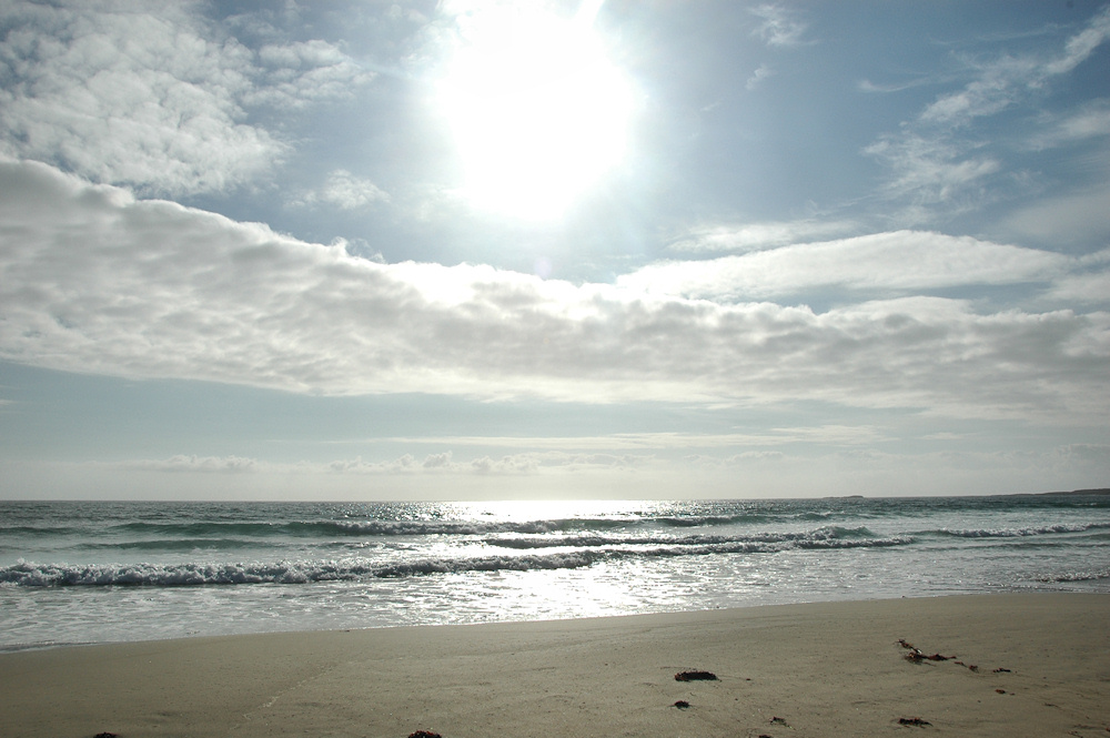 Picture of a view over a beach out to sea with a bright sun above but also some clouds in the sky