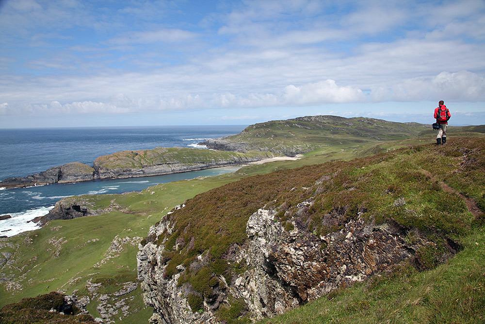 Picture of a man walking on a hill overlooking a dramatic coastline with a small beach