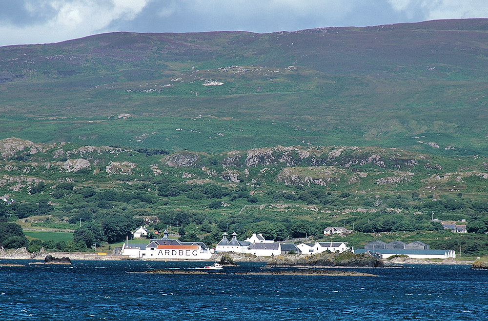 Picture of a coastal distillery at the foot of hills, a small boat passing