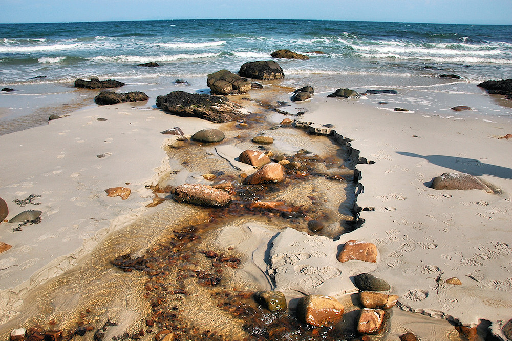 Picture of a burn running over a beach with stones and pebbles into the sea