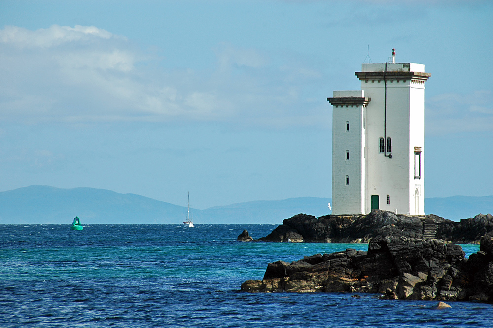 Picture of a square lighthouse and a green buoy with an approaching sailing yacht