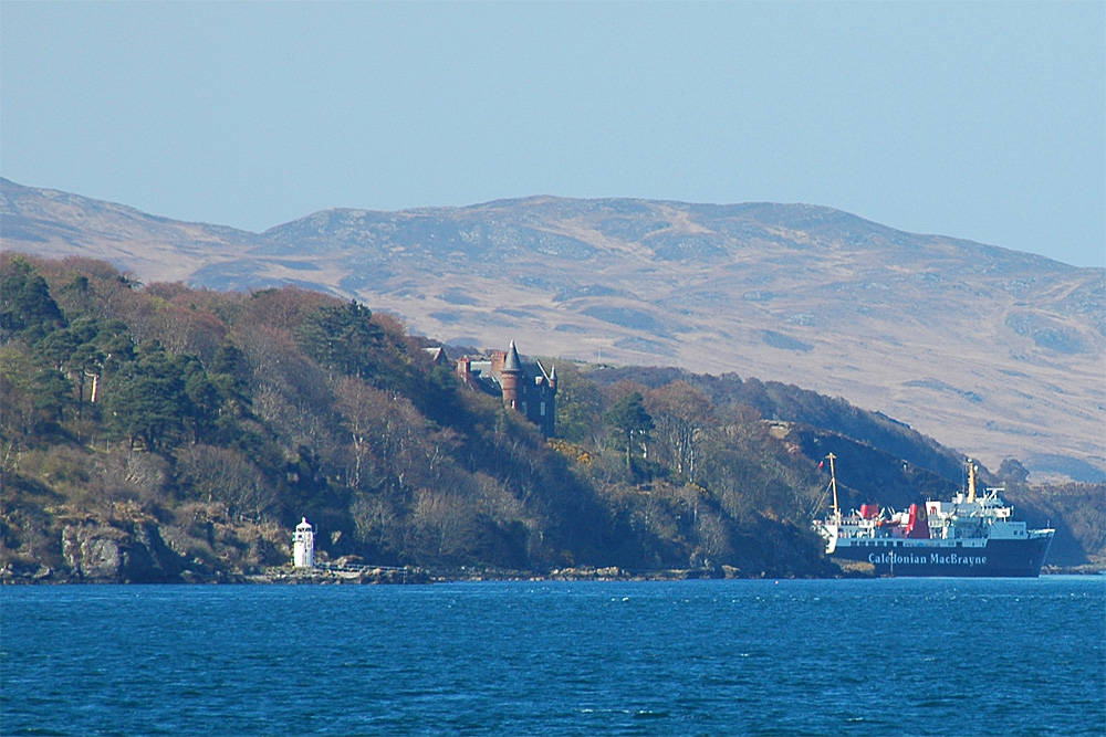Picture of a small lighthouse in a sound, behind it a stately home and a berthed ferry